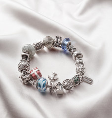 silver bracelet with charms on grey background