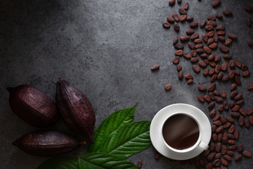 Hot chocolate and Cocoa pod cut exposing cocoa seeds on dark table, top view with copy space
