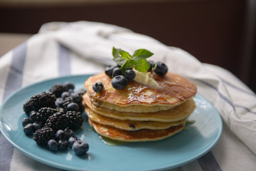 Pancakes with blackberries and blueberries on a blue plate