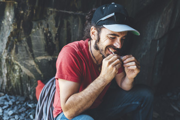 Mid aged man rolling a cigar with beard and a cap seated in a cave at Dinorwic Quarry at Snowdonia National Park in North Wales