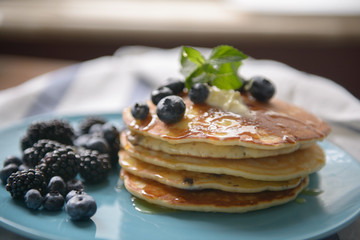 Pancakes with blackberries, blueberries and mint on a blue plate