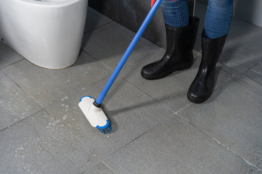 hand using brush to cleaning the tile in bathroom