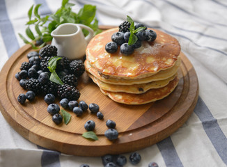 Pancakes with blackberries, blueberries and mint on the kitchen board - top view