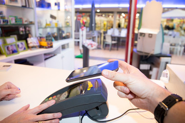 Man paying bill through smartphone using NFC technology mobile payment