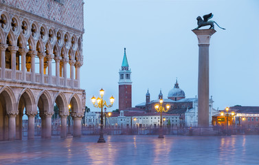 Venice evening city view of Square Piazza San Marco, Doge's Palace, column of winged Lion, gondolas wharf and San Giorgio Maggiore island with basilica and campanile in light of streetlights