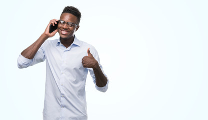 Young african american man using smartphone happy with big smile doing ok sign, thumb up with fingers, excellent sign