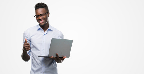 Young african american businessman using computer laptop happy with big smile doing ok sign, thumb up with fingers, excellent sign