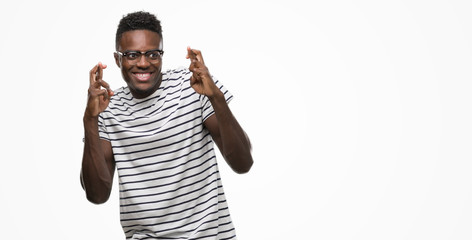 Young african american man wearing glasses and navy t-shirt smiling crossing fingers with hope and eyes closed. Luck and superstitious concept.
