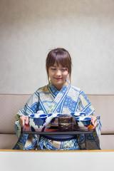Woman wearing traditional japanese yukata or kimono make a tea in japan style.