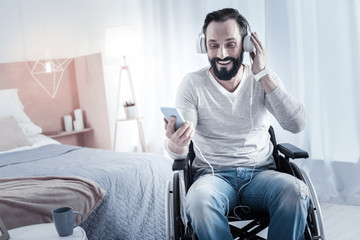 Joyful mood. Kind bearded male touching headphones while watching video