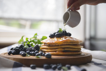 Pancakes and berries on the board with honey