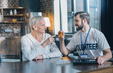 Healthcare. Good-looking exuberant bearded man smiling and holding some pills while talking with an old man