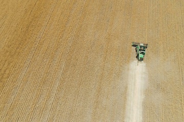 Modern combine harvester working on the wheat crop. Aerial view.