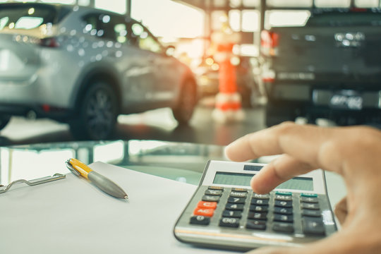 man pressing calculator for business finance on car showroom blurry background.for automotive automobile or transportation transport