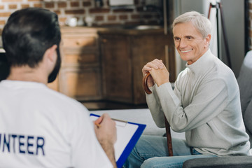 I feel happy. Inspired kind grey-haired man smiling and sitting with his stick while talking with a volunteer