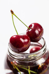 Fresh cherries on a glass jar in a white background