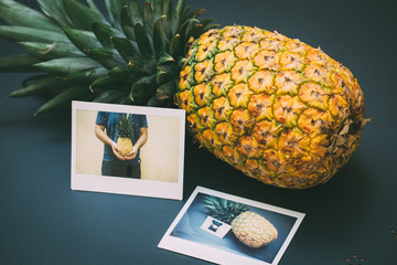 Juicy pineapple with two instant photos on a black table, outdoors.