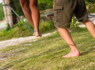 Woman keeping balance on slackline with help from a man at the beach in the island of Koh Phangan, Thailand. Learning process, doubtful, dare, equilibrium concepts