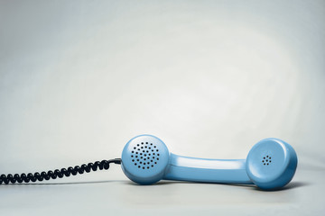 Blue telephone on blue background