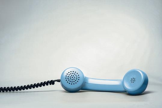 Blue telephone on blue background