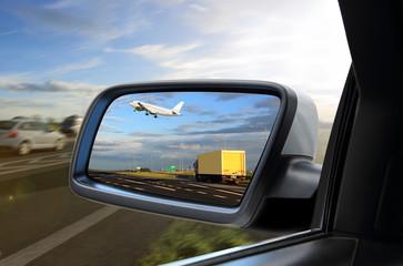 Widok w lusterku samochodu osobowego jak samolot wznosi sią nad ciężarówką .