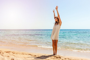 Woman relaxing at beach enjoying summer freedom. Happ girl at the beach