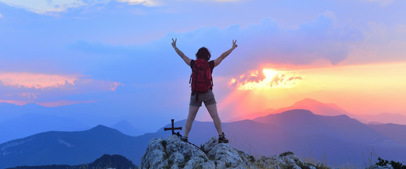 Woman who hiker reaches the top at sunset