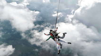 Foto auf Acrylglas Luftsport Skydiving tandem falling into the clouds
