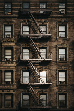 Facade of a typical New York block of flats with fire escape at the front, sun reflects in the windows.