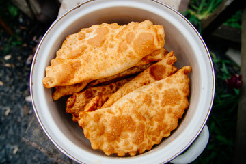 The process of cooking chebureks. The Caucasian and eastern food is a patty made from thin unleavened dough with stuffed lamb and spicy seasonings. Cheburek - fried pie with meat and onions.