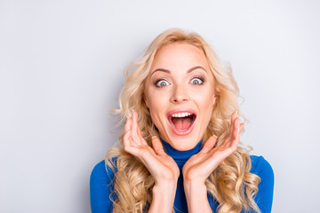 Portrait of sexy, surprised, impressed, stylish, pretty, cute, charming, nice, blonde woman in blue turtleneck  with wide open eyes and mouth looking at camera holding hands near face