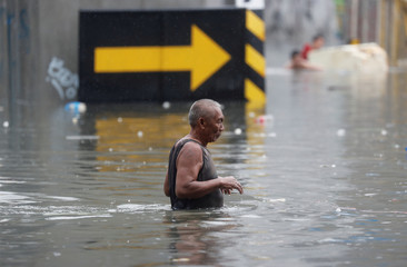 A resident wades along a flooded street caused by monsoon rains and Tropical Storm Son-Tinh in Quezon city, Metro Manila