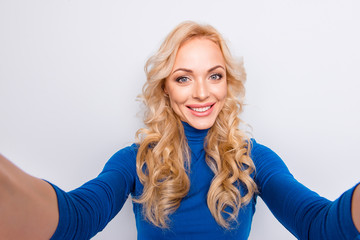 Self portrait of pretty, trendy, charming, lovely, nice, sexy, cute, blonde woman in blue turtleneck isolated on grey background shooting selfie with two hands on front camera