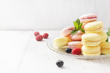 Different types of macarons on white wooden table. Copyspace.