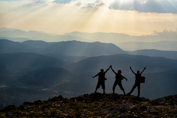 joyful happiness at the peak of three adult men and mountains