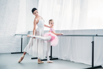 beautiful child in pink tutu practicing ballet with young teacher in ballet studio