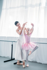 adorable child in pink tutu practicing ballet with young teacher in ballet school