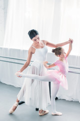 high angle view of adorable child in pink tutu practicing ballet with young teacher in ballet school