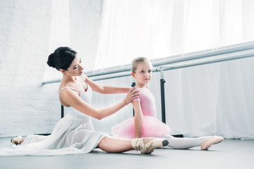 adorable little ballerina in pink tutu sitting and stretching while training with ballet teacher in studio