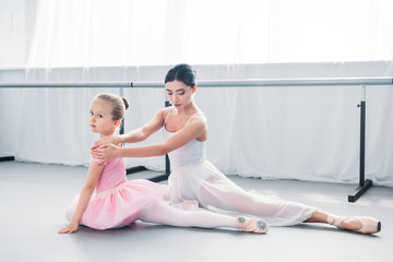 adorable little ballerina in pink tutu looking at camera while exercising with teacher in ballet school