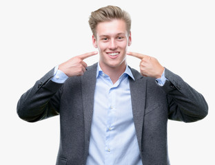 Young handsome blond business man smiling confident showing and pointing with fingers teeth and mouth. Health concept.