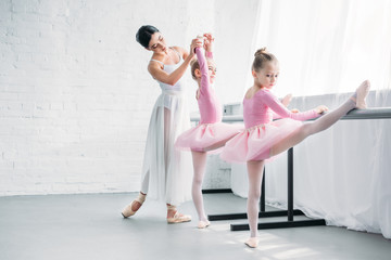 beautiful young ballet teacher exercising with kids in ballet school