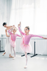 ballet teacher exercising with small dancers in ballet school