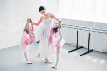 smiling young ballet teacher exercising with kids in ballet school