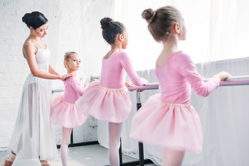 cute little kids in tutu skirts exercising with teacher in ballet school