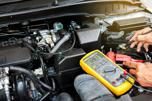 Car Mechanic Is Using A Multimeter With Voltage Range Measurement To