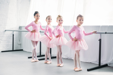cute multiethnic kids in pink tutu skirts exercising and smiling at camera in ballet studio