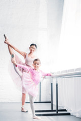 smiling young ballet teacher looking at little student stretching and looking at camera in ballet studio