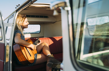Girl playing guitar inside a van