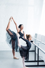 side view of young ballet teacher and little student stretching together in ballet school